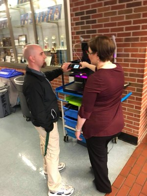Principal Travis Langley talking to rep about 3D printing.