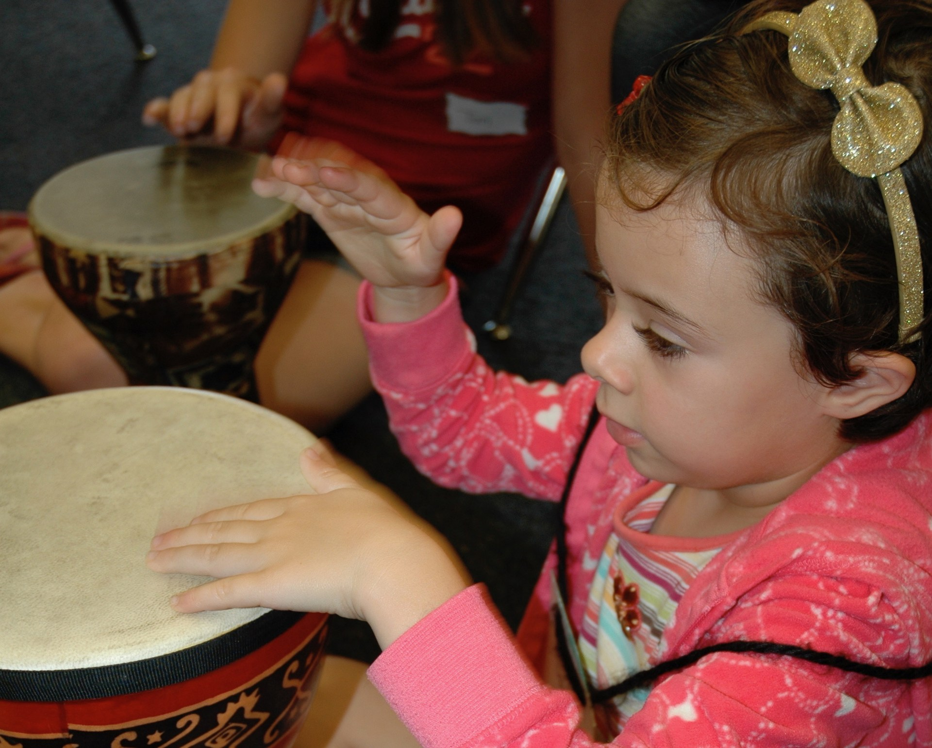 A girl beating on a drum.