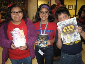 students holding books donated by molina foundation