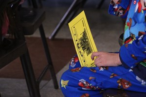 Student in pajamas holding his Polar Express train ticket.