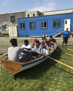 Students sitting in the boat on land learning how to row