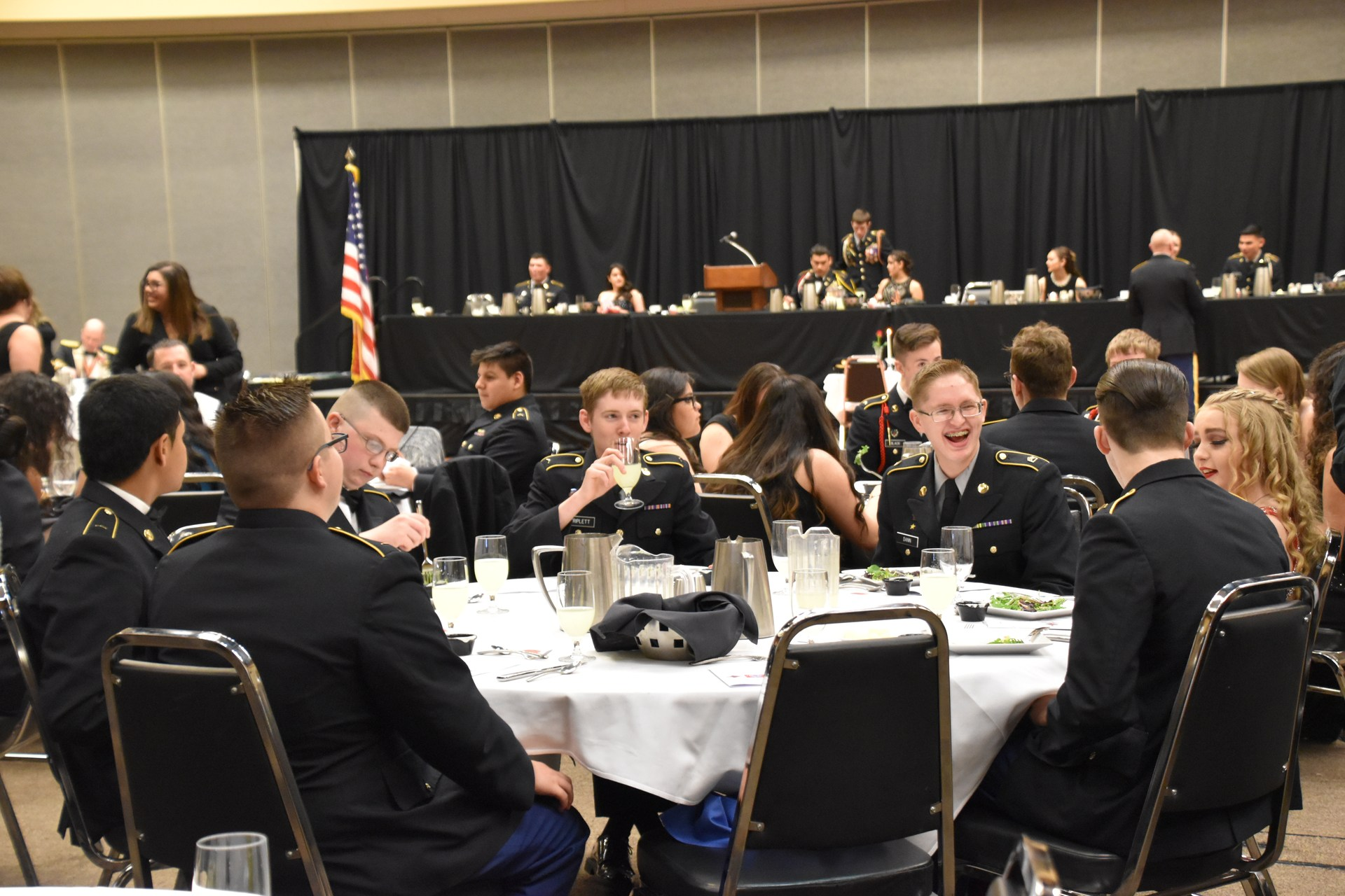 Table of East Valley JROTC members chatting at dinner.