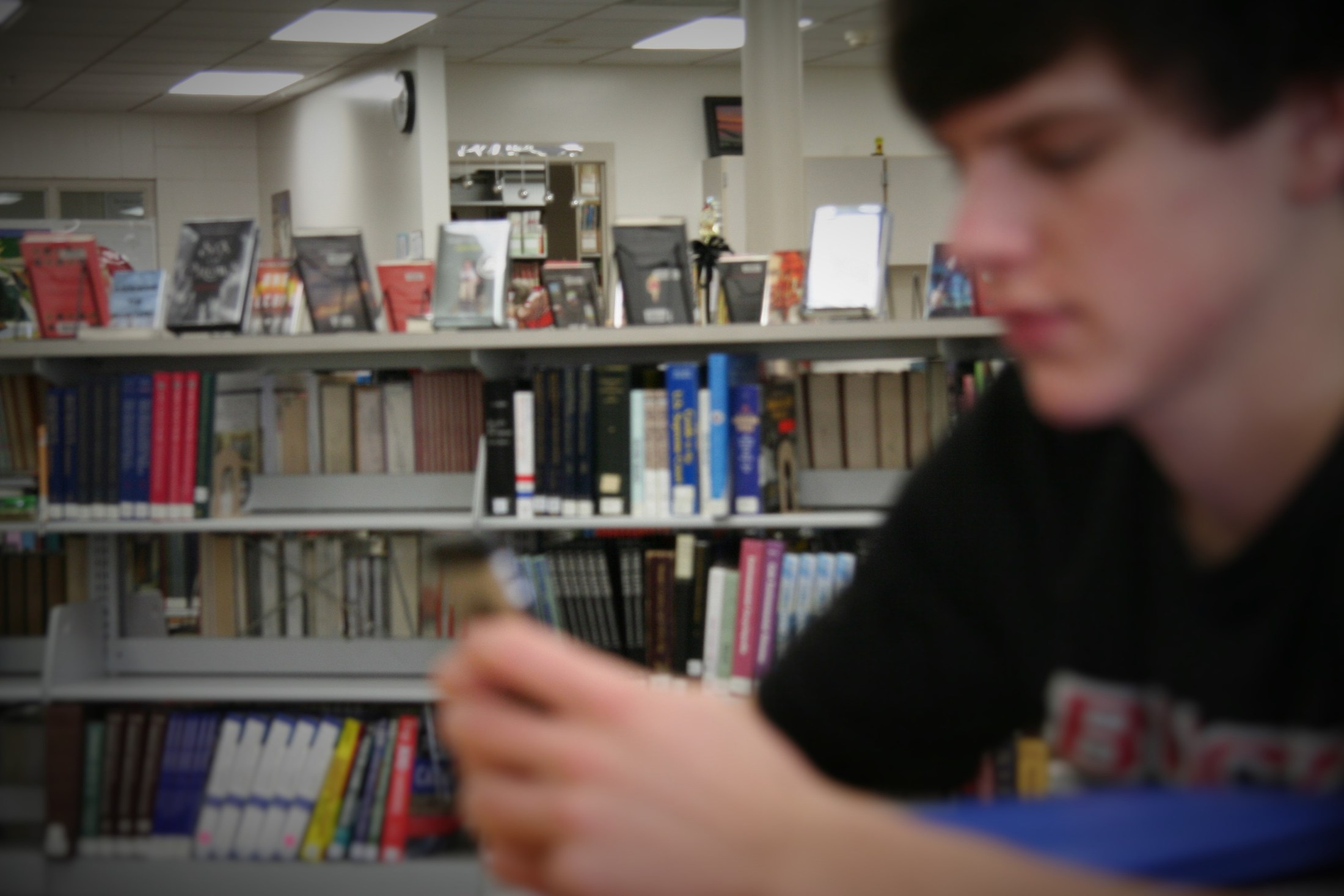 Student in foreground out of focus and books in focus in background