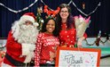 Paz Assistant Principal Shamilya Woods with presenting Santa Claus and benefactor Gina Ruffolo VanValkenburgh with a thank you card from students.