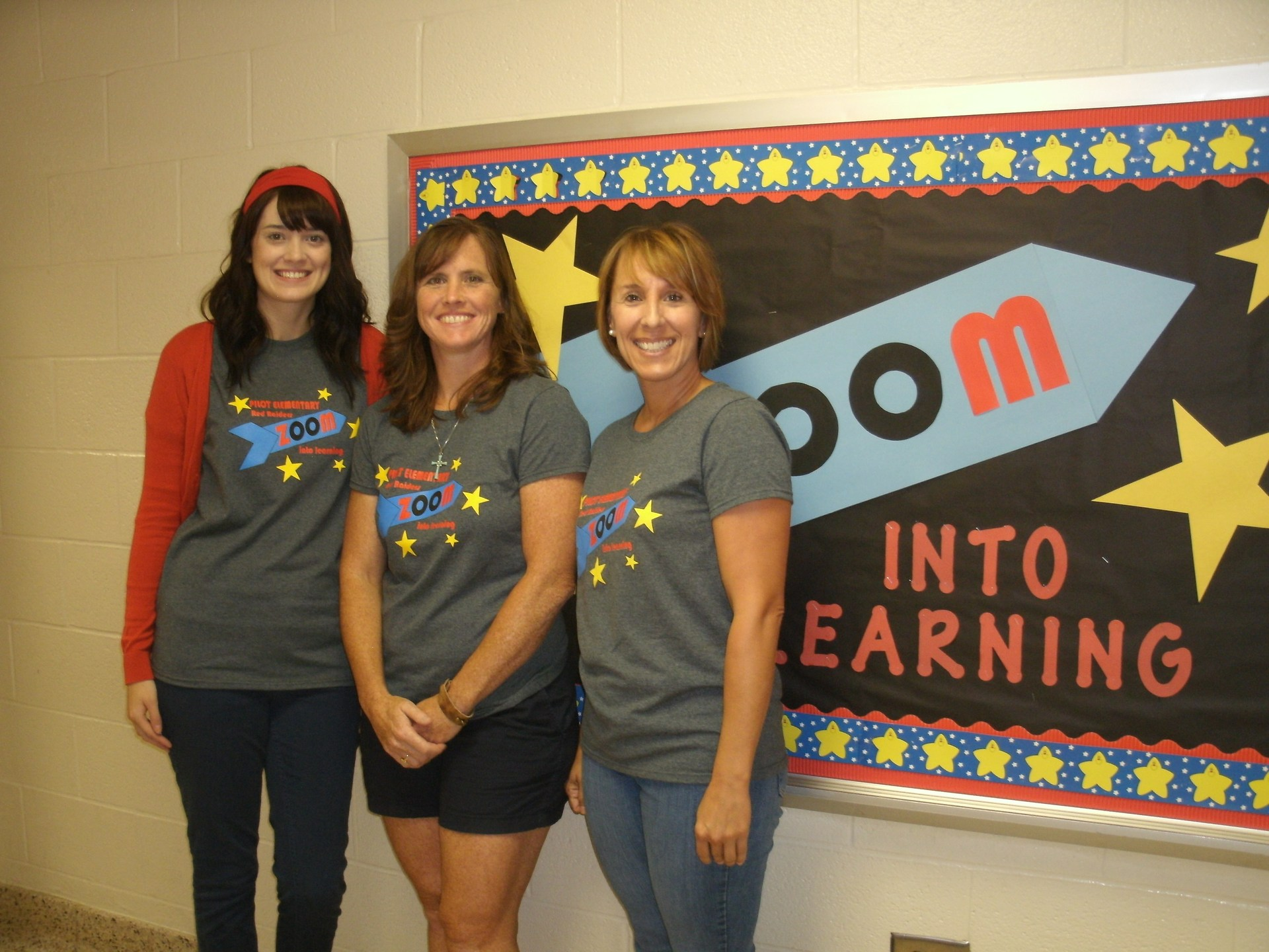 Two speech teachers and a resource teacher stand in front of a bulletin board.
