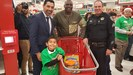 Superintendent with student and parent, holding a shopping cart at local Target Store.