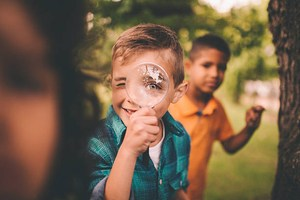 Smiling boy with magnifying glass