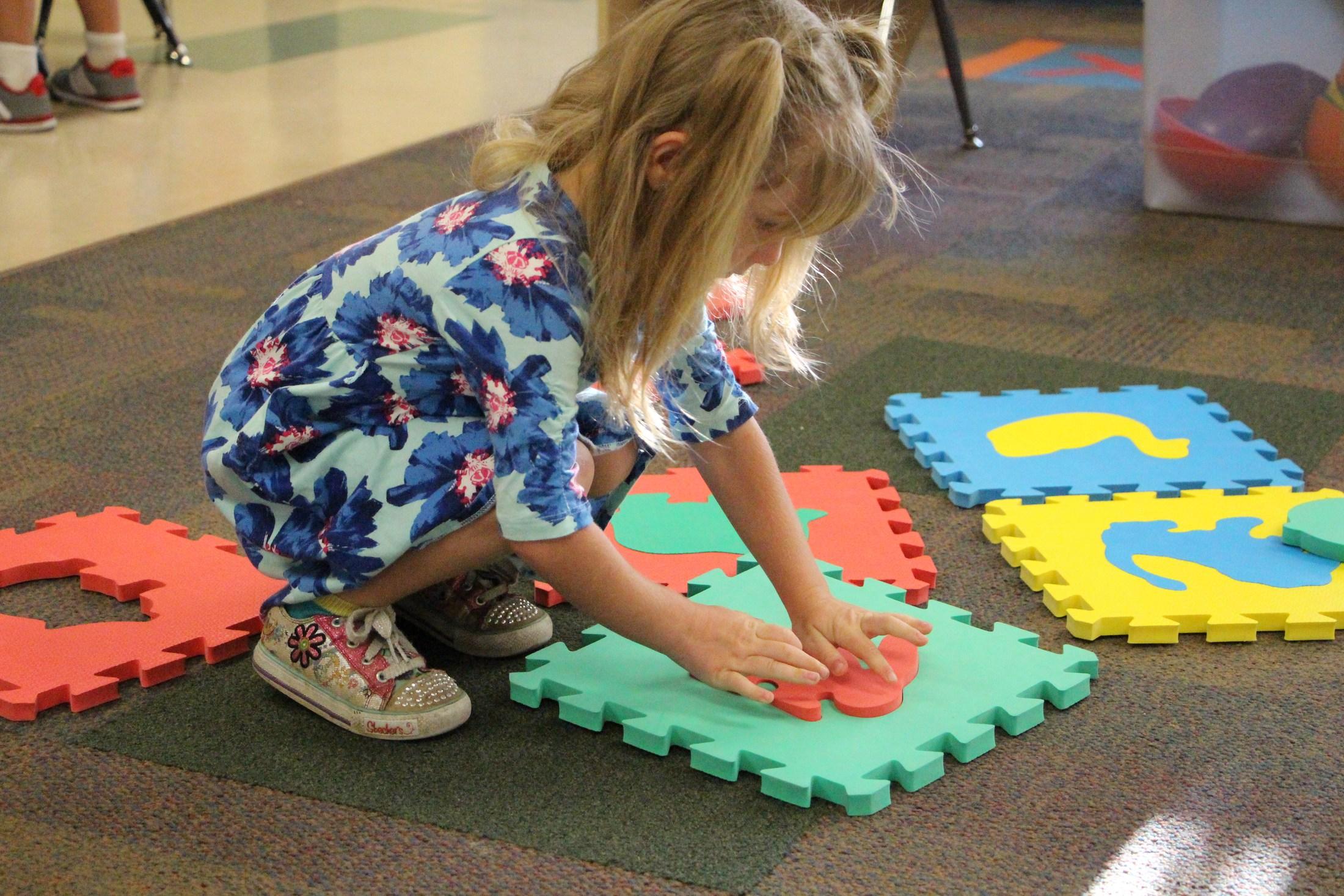 Preschool student completes a puzzle.