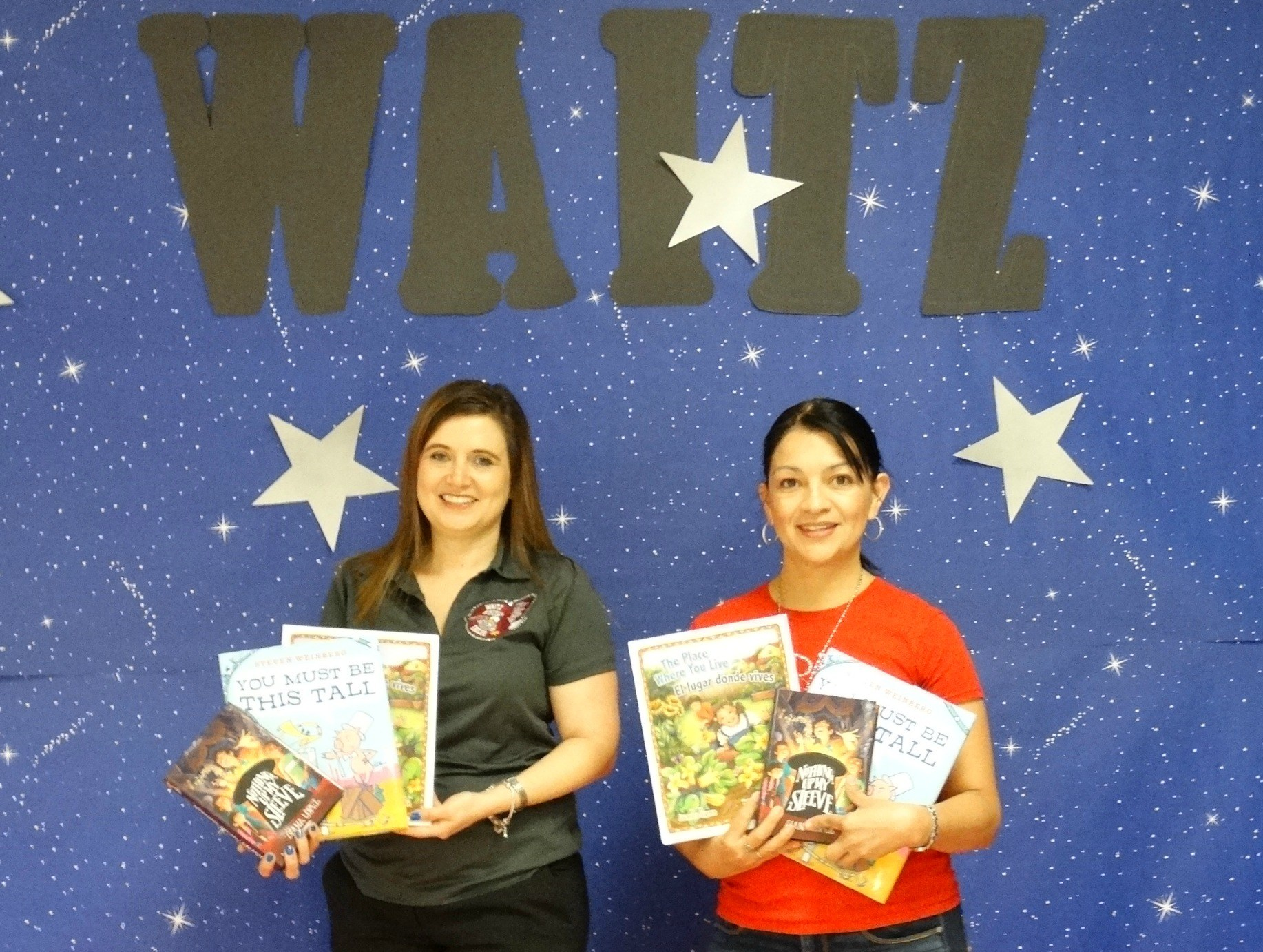 Librarian and library clerk showing the Reading Rock Star books.