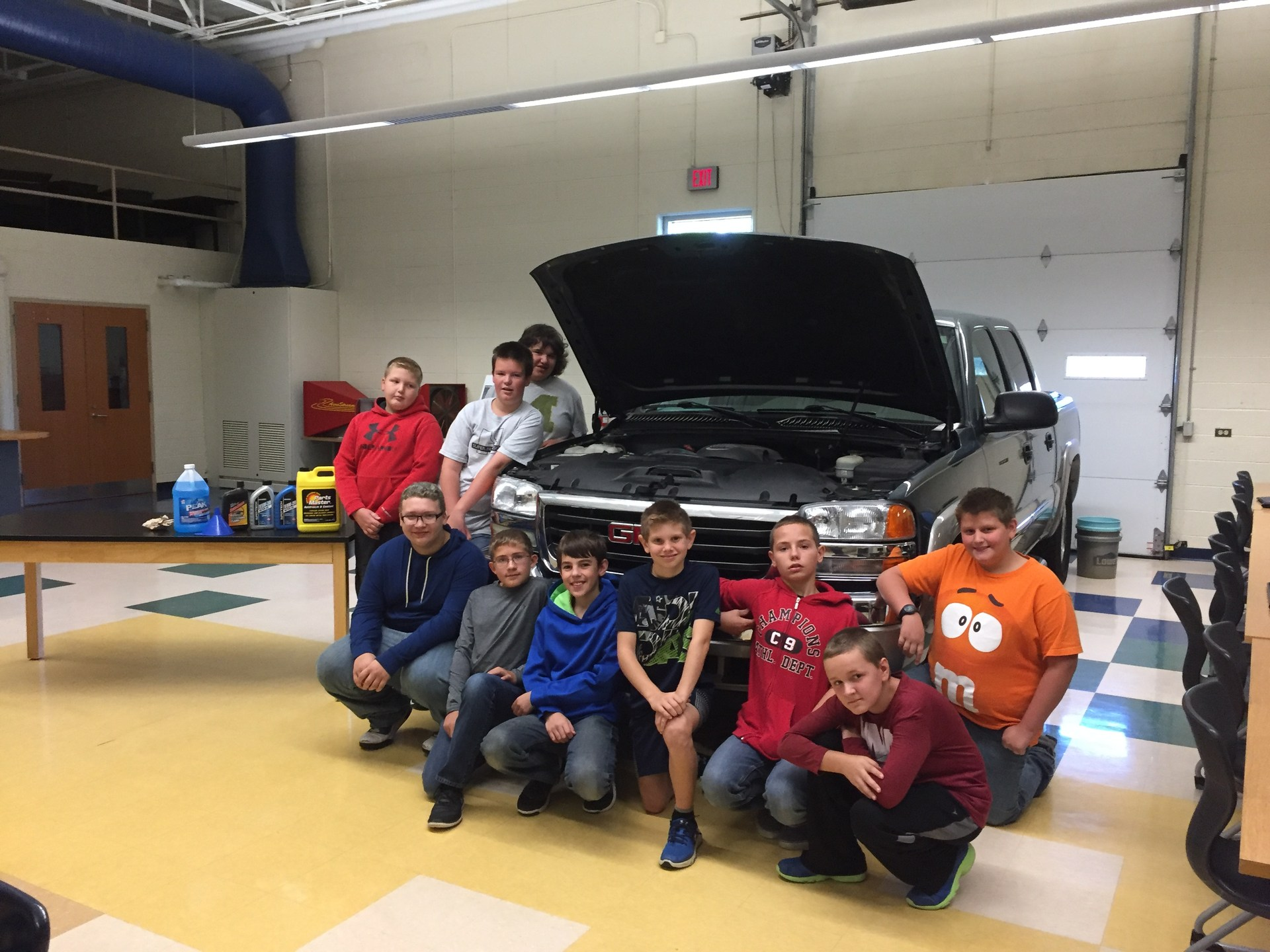 Students pose by a car that they used to learn how to do an oil change.