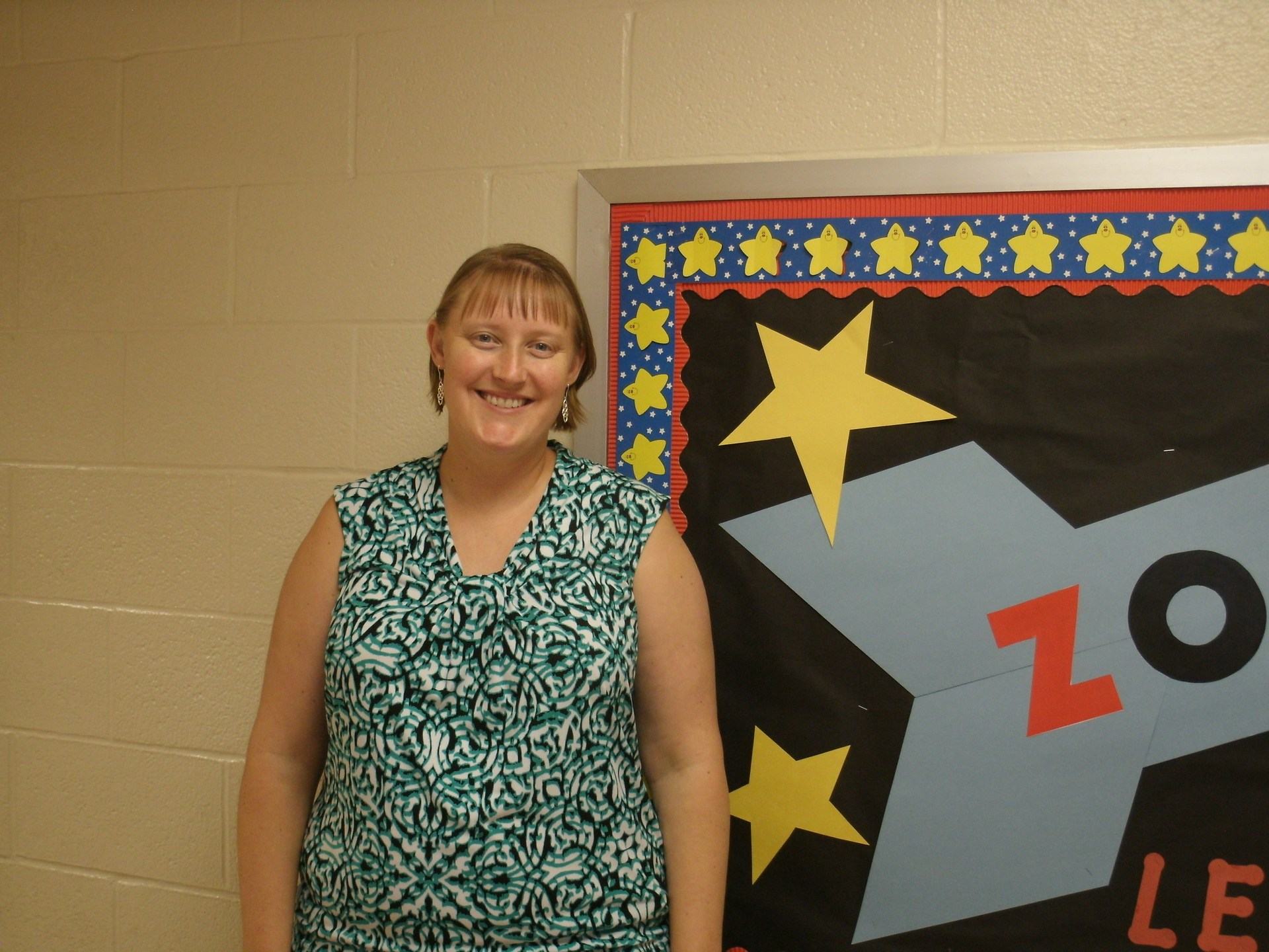 Mrs. Haynes is standing in front of a bulletin board.