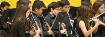 several students seated playing woodwind instruments