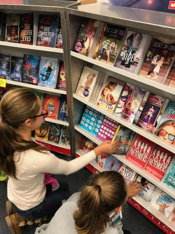 Two girls looking at books