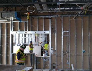 Construction crew members working in two rooms dividing by steel framing and drywall