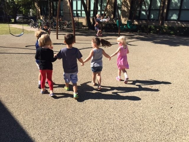 Four elementary students walk hand in hand to the swing set on the campus playground