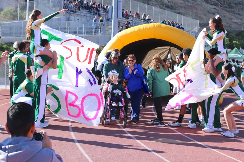 Special Education students running through the Super Kids Bowl banner.