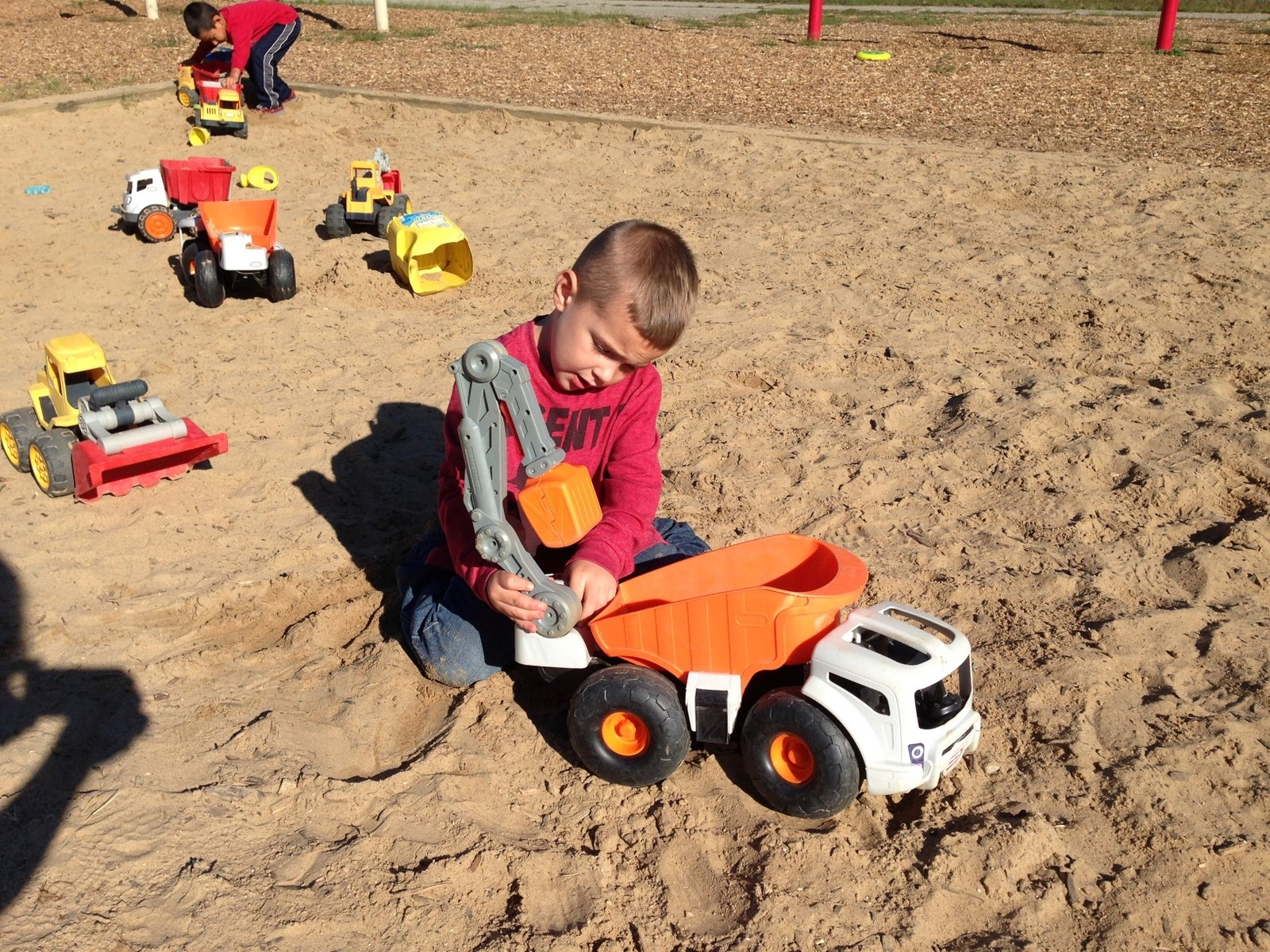 Preschoolers outside in a sandbox