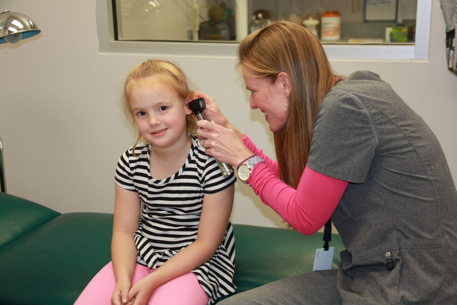An Elementary School Nurse checks the ears of one student in the campus clinic