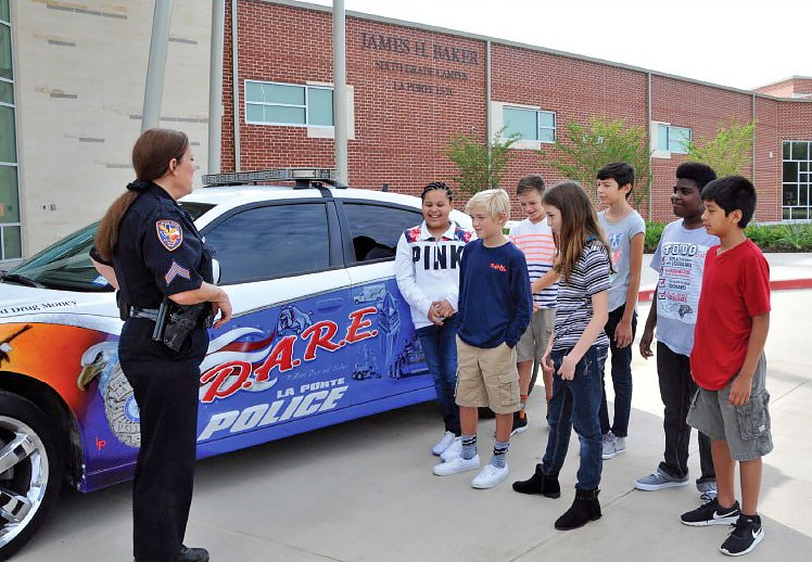 Police officer talking with students. All are standing adjacent to police car.