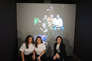 CREW members posing before a projection of a video conference group screen