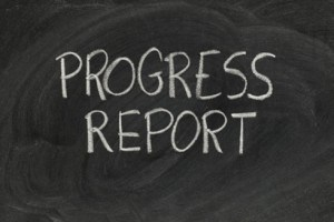 black chalk board with white chalk letters reading progress report