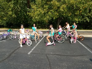 Girl scouts in a parking lot with bicycles