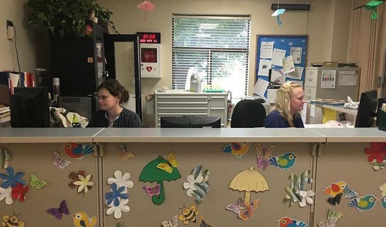 Health Center staff sit behind counter