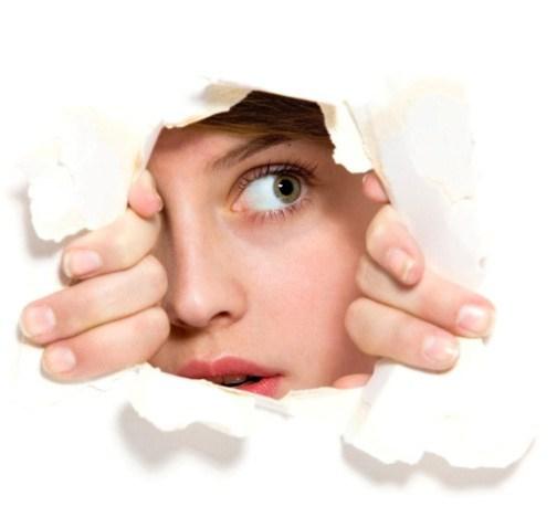 Woman peeking through ripped paper