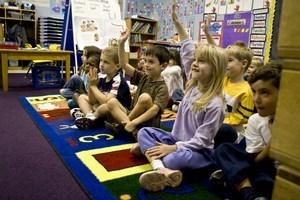Kids sitting on carpet in Kindergarten classroom.