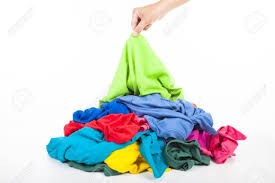 a hand picking up shirts in a pile