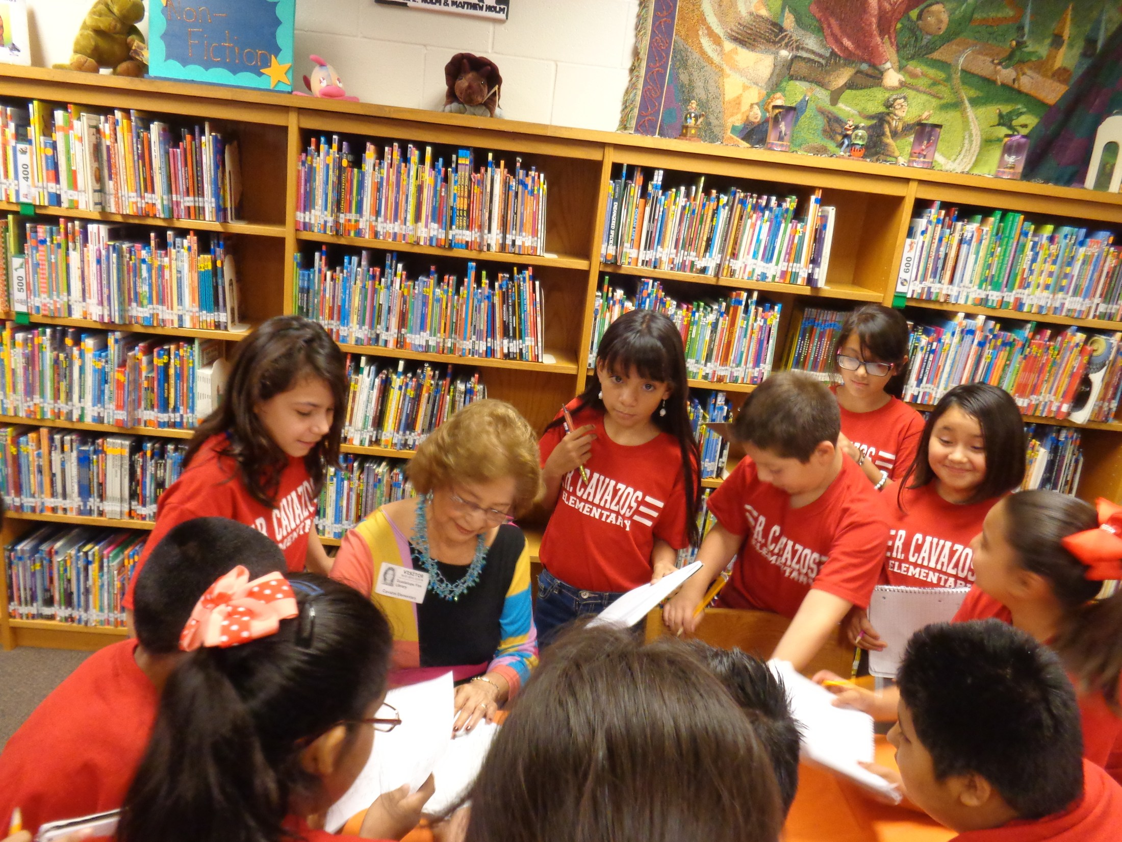 Author signing book with students