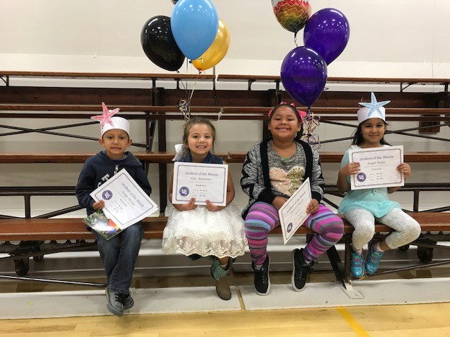 Students pose with student of the month certificates