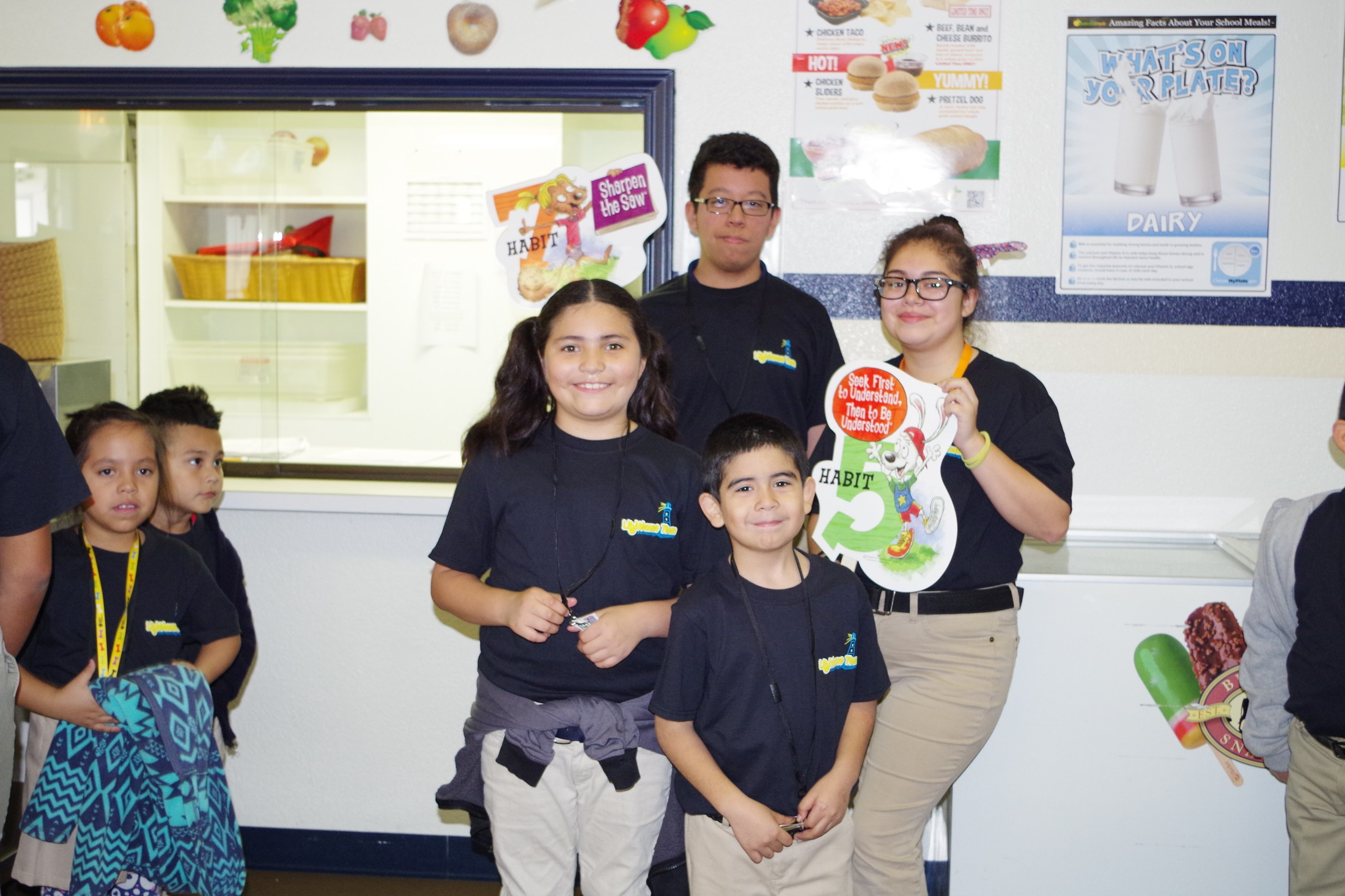 Students posing with 7 habits poster