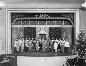View of the stage of the old auditorium with many people singing.