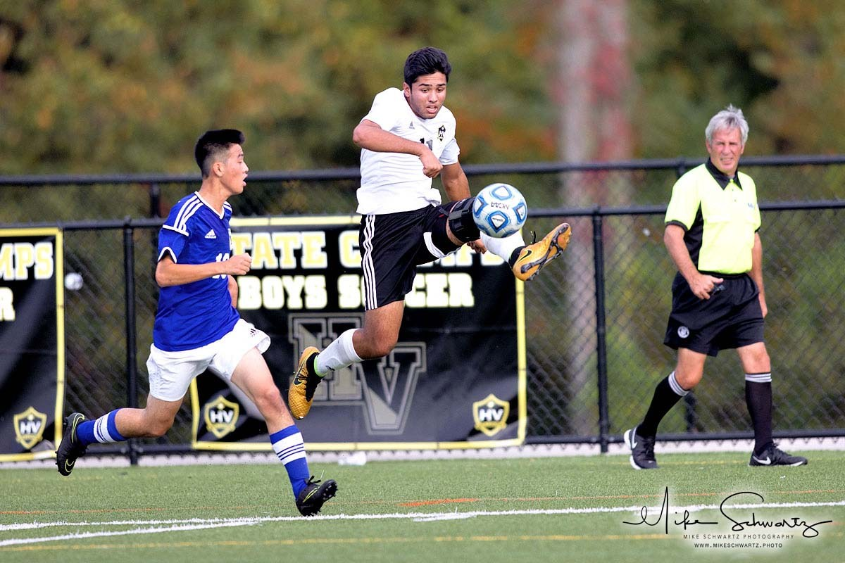 CHS boys soccer player leaps in air to kick ball