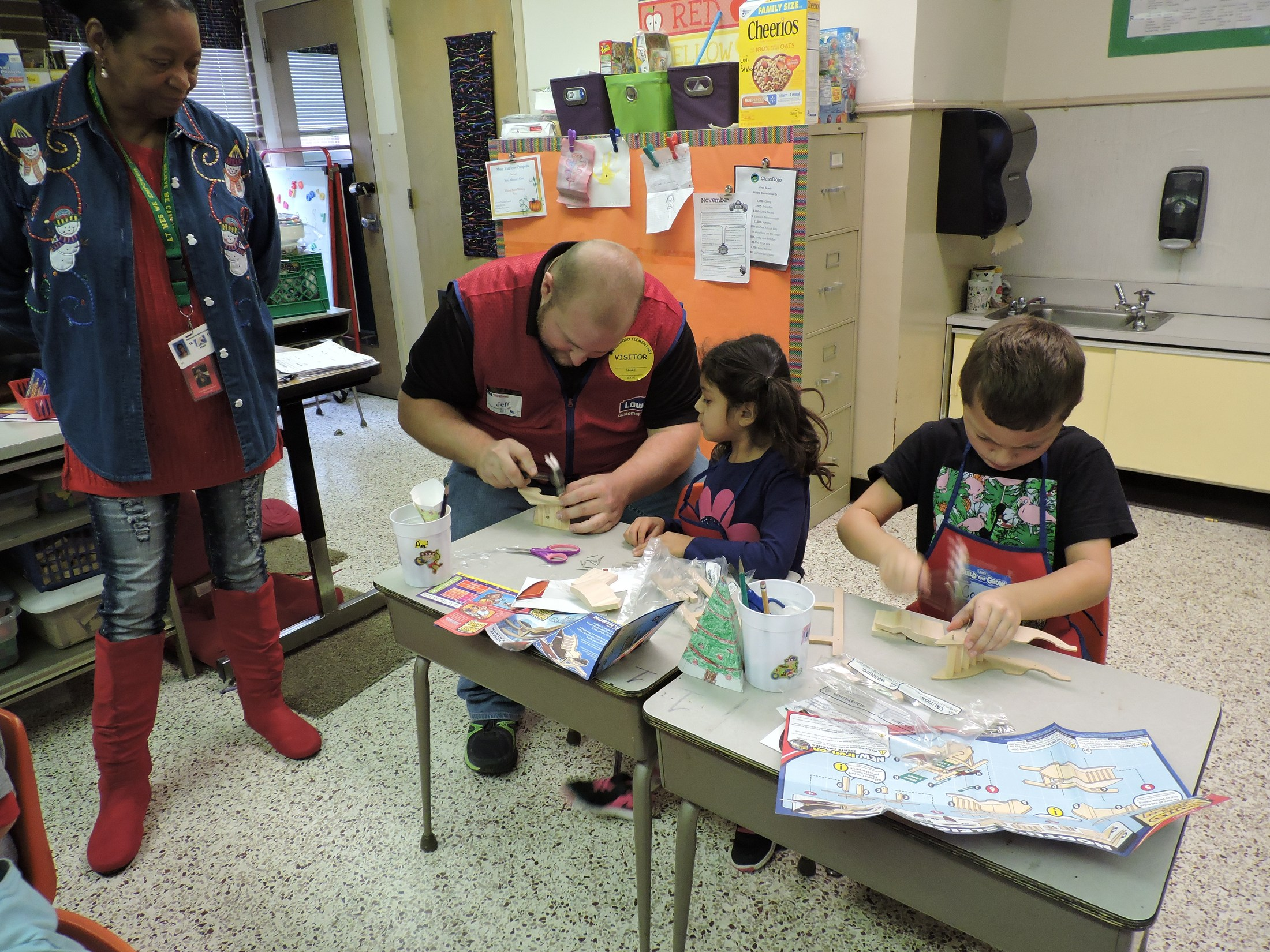 Lowe's personnel helping students build sleds