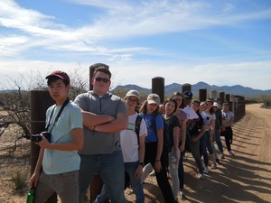 students lined up at the US Border fence which is just a barbed wire fence at this section