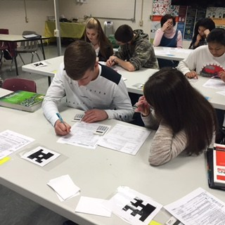 two students working on taxes: Tax Time: Working on our 1040 EZ tax form!