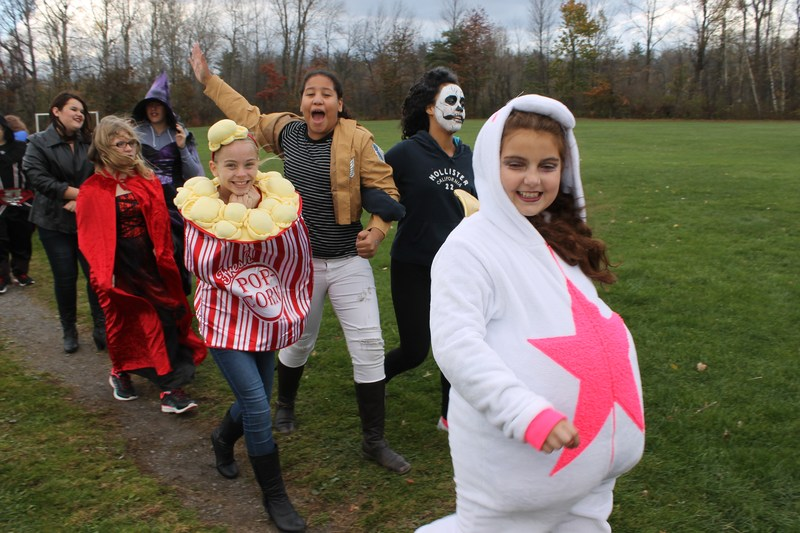 Line of elementary students walking outside wearing various halloween costumes