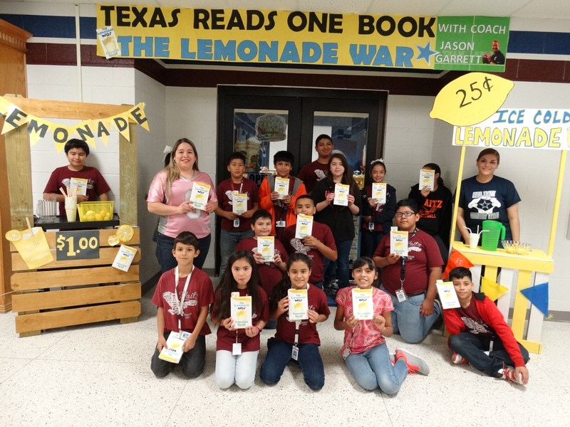 Waitz students standing in front of the library showing their book copies of The Lemonade War, with lemonade stands on each side of the door.