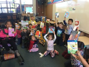 Students hold up books from the Reading is Fundamental distribution