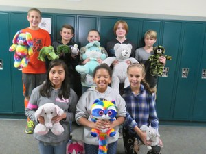 Students display some of the stuffed animals they collected.