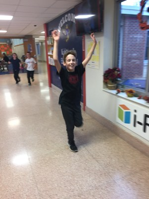 elementary student runs with both arms raised in a school hallway