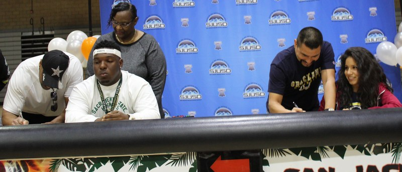 Parents of Elijah Chambers and Soleya Figueroa sign their students' college acceptance offers.