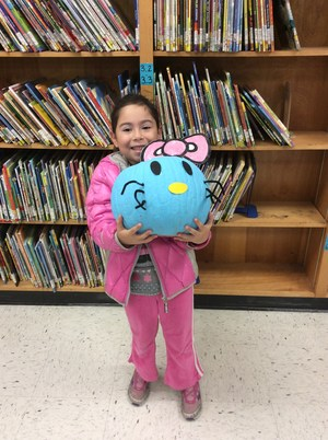 Student posing with her pumpkin in the library.