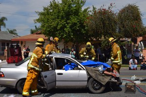 "Los Angeles County firefighters demonstrate the dark reality of removing victims from automobiles totaled on impact for a simulated crash during Sierra Vista High School's ""Every 15 Minutes"" program on April 26. Equipped with saws and the Jaws of Life, firefighters remove doors to retrieve injured students."