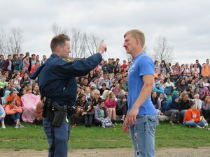 A Michigan State Police trooper initiates sobriety tests during the mock accident scene.