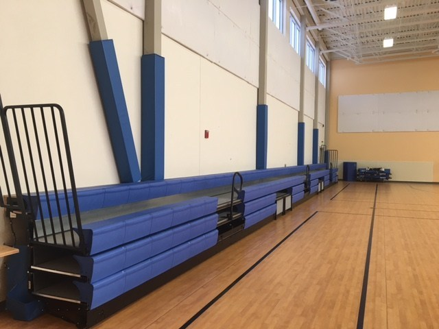 Blue bleachers line the wall of the gym