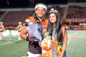 Homecoming queen and king standing on football field