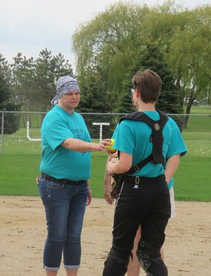 Cindy Stickney accepts a game ball from the TKHS catcher.